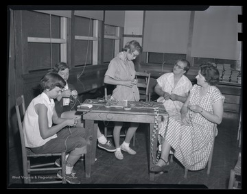 A girl tries on a hand-made belt while her companions weave threads together. Subjects unidentified.