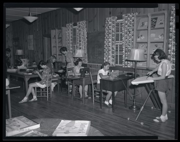 A group of unidentified girls sit behind sewing machines as they work through their class activity.