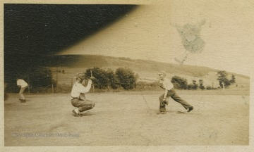 Two boys practice catching and throwing on the baseball field. Subjects unidentified.