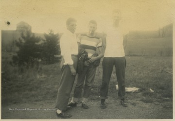 Three boys on the baseball team pose together for a group photo. Subjects unidentified.