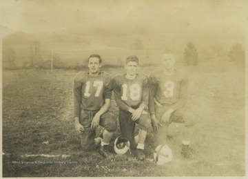 Frank Lambert (left), Richard Fraley (center), and Paul R. Cooper, Jr. (right) pose together in their football uniforms.