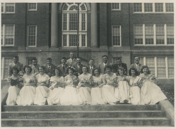 A group of male and female students pose together on the steps outside of the high school building. Subjects unidentified.