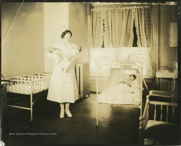 A nurse holds a baby in each arm. On the right of the photograph, a child sleeps in a crib.