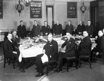 Executives of the Chevrolet Company gather around a table. In the background are Chevrolet advertisements.