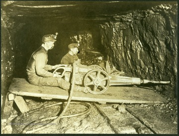 """The miner is using a compressed-air drill to drive a hole in the lower edge of the working face of the coal vein."""