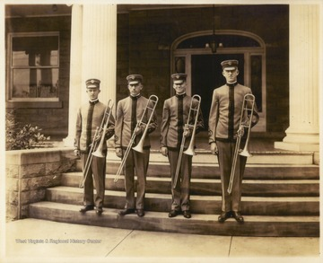 Photograph of four Cadet Band members on the steps of Purinton House, which was then home to the university president.  Pictured are, left to right, Herbert Lynn McLaughlin, Edgar Frank Heiskell, O. D. Gill, and M. H. Thorn.