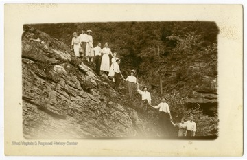 A group of young men and women pose on a rocky hillside near the Cheat River, W. Va.