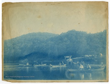 "A group of men pend time in boats on the Cheat River. The banner in the background reads in part, ""Elkhorn Hunting."""