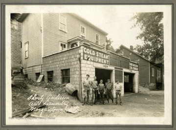 "A group of boys pose outside of Shorty Anderson's Auto Laundry. Text on back reads, ""University Ave. Zackquill Morgan home on the right."""