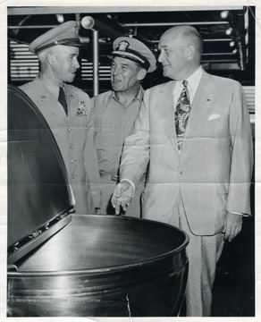 General Omar N. Bradley, Admiral Edward C. Ewen, and Secretary of War Louis A. Johnson discuss the military crisis in Korea around a steam kettle in Guam.