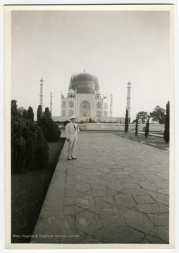 A view of the Taj Mahal, showing wartime air raid protection measures on the central dome. The man is likely Louis Johnson.