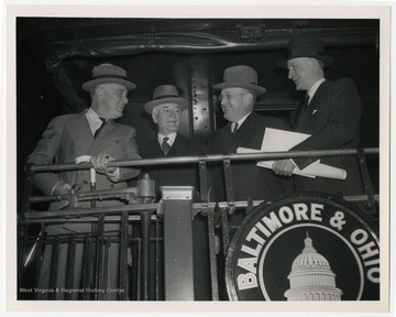President Franklin Roosevelt pictured with Secretary of State Cordell Hull, Assistant Secretary of Defense Louis A. Johnson, and an unidentified man.