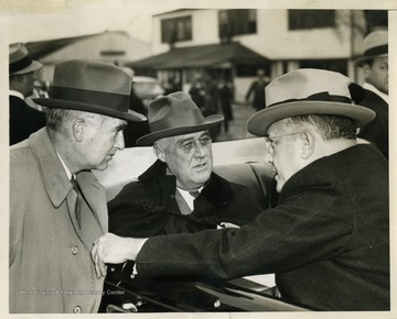 "Text on the back reads: ""Charles Edison, Assistant Secretary of the Navy; President Roosevelt; and Louis Johnson, Assistant Secretary of War, as the President made an inspection of various types of aircraft at Army's Bolling Field and Naval Air Station."""