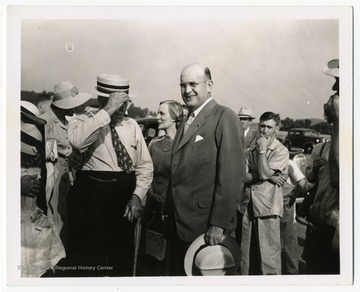 Assistant Secretary of War Louis Johnson (center, bareheaded) attends the opening of an airline at the Harrison County Airport, now known as the Benedum Airport.