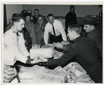 """Members of the Charleston Salvation Army (right) distribute food to the needy, made available under the U.S. Department of Agriculture's increased food distribution plan. Canned pork and gravy, dried beans, dried eggs, and peanut butter have been added to the other abundant foods being distributed in areas where needs are pressing, particularly in areas of high unemployment."" USDA office of information photograph."