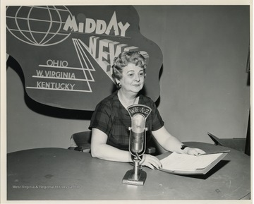 """Katie Doonan shown at her studio where she announced the dates that abundant agricultural commodities would be distributed to the needy in the Charleston area. The stepped-up distribution of food was caused by President Kennedy's Executive Order Number 1, which added protein foods to the list of commodities being distributed."" United States Department of Agriculture Office of Information."